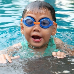 Image of a child swimming in a pool with a link to SwimEngland