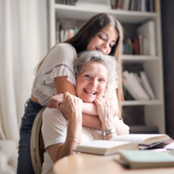 Image of elderly lady with younger woman giving a hug, links through to the mental health and well-being page